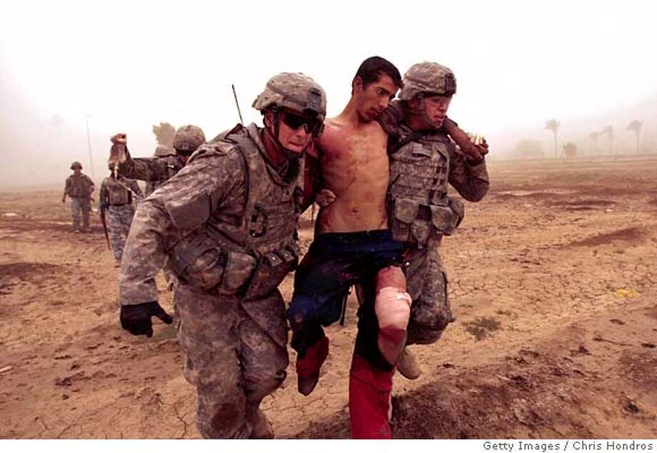 ###Live Caption:BAGHDAD, IRAQ - MAY 16: In the fog of an Iraqi sandstorm, medic Sgt. Matthew Kunkle (L) and Private Aaron Livas of the US 2nd Battalion, 30th Infantry Regiment of the 10th Mountain Division carry a wounded Iraqi man during a routine morning patrol on May 16, 2008 in Baghdad, Iraq. When the patrol encountered a group of three men digging in an area of frequent insurgent mortar activity, the wounded man started to run and was shot in the leg. He was immediately treated by the US medic travelling with the platoon and transported to the nearest US base for medical care, and is expected to recover. The other two men were arrested and later released. (Photo by Chris Hondros/Getty Images)###Caption History:BAGHDAD, IRAQ - MAY 16: In the fog of an Iraqi sandstorm, medic Sgt. Matthew Kunkle (L) and Private Aaron Livas of the US 2nd Battalion, 30th Infantry Regiment of the 10th Mountain Division carry a wounded Iraqi man during a routine morning patrol on May 16, 2008 in Baghdad, Iraq. When the patrol encountered a group of three men digging in an area of frequent insurgent mortar activity, the wounded man started to run and was shot in the leg. He was immediately treated by the US medic travelling with the platoon and transported to the nearest US base for medical care, and is expected to recover. The other two men were arrested and later released. (Photo by Chris Hondros/Getty Images)###Notes:US Troops Treat Iraqi Man Shot As He Fled From a Patrol###Special Instructions: Photo: Chris Hondros