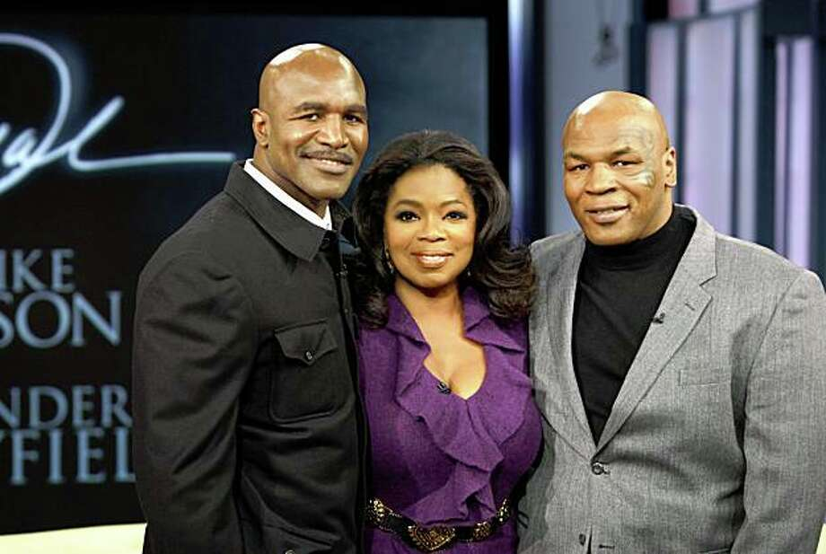 """In this photo provided by Harpo, Inc., talk-show host Oprah Winfrey poses with former world champion boxers Mike Tyson, right, and Evander Holyfield on a live episode of """"The Oprah Winfrey Show,"""" Friday, Oct. 16, 2009, in Chicago. Photo: George Burns, AP"""
