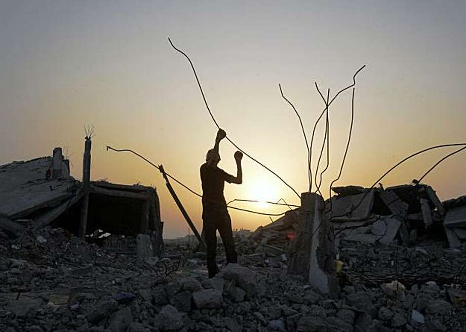 A Palestinian removes building materials from a house destroyed in January's Israeli military offensive, in Jebaliya, northern Gaza Strip, Friday, Oct. 16, 2009. The U.N. Human Rights Council voted Friday to endorse a Gaza war crimes report and send it to the Security Council, possibly setting up international prosecution of Israelis and Palestinians accused of war crimes. (AP Photo/Hatem Moussa) Photo: Hatem Moussa, AP