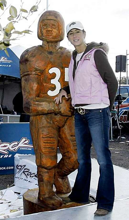 In this photo taken Sunday Oct. 11, 2009, carvings for a cause founder Theresa Forton-Barnes poses with a carving of former Buffalo Bills running back Thurman Thomas. The chain saw carving of Thomas is missing from a parking lot across from Ralph Wilson stadium Monday Oct. 12, 2009, a day after it was unveiled.  (AP Photo/Buffalo News, John Hickey)  ** MANDATORY CREDIT, TV OUT, MAGS OUT ** Photo: John Hickey, AP