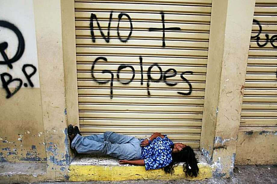 """FILE - This Oct. 5, 2009 file photo shows a woman sleeping under graffiti that reads in Spanish  """"No more coups"""" in Tegucigalpa, Honduras. Nearly four months after the military ousted President  Manuel Zelaya, Hondurans are feeling the sting of a political crisis that is eroding an already fragile economy and increasing hunger in one of the Western Hemisphere's poorest countries. (AP Photo/Rodrigo Abd, file) Photo: Rodrigo Abd, AP"""