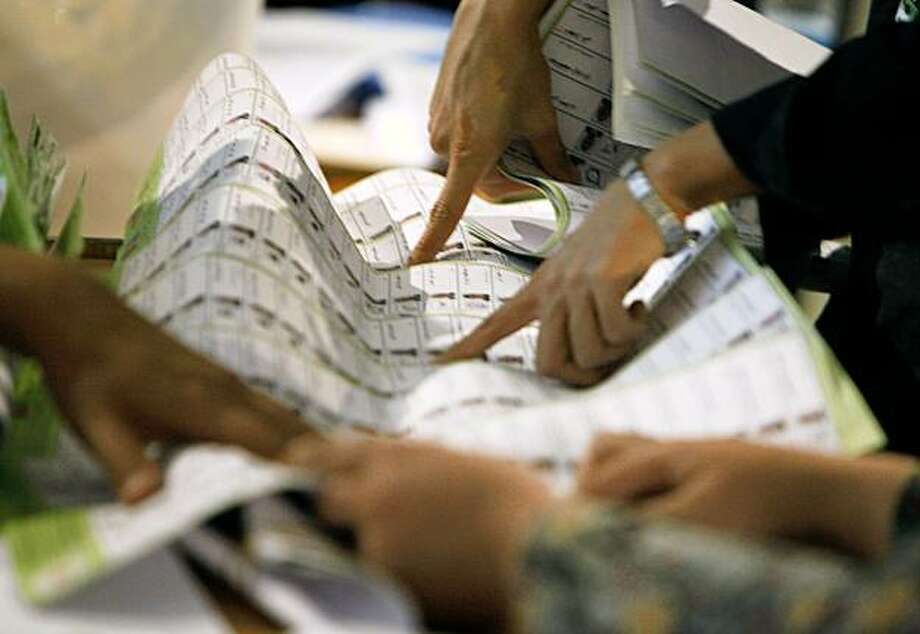 Workers of the Afghan Election Commission check suspicious ballot papers during the recounting process at the main election office in Kabul, Afghanistan on Wednesday, Oct. 7, 2009. Election workers have begun recounting ballots from the disputed Aug. 20 presidential election Monday, as Afghan President Hamid Karzai's top challenger Abdullah Abdullah has already expressed his deepest concerns over the massive frauds of the presidential election of the country. (AP Photo/Musadeq Sadeq) Photo: Musadeq Sadeq, AP