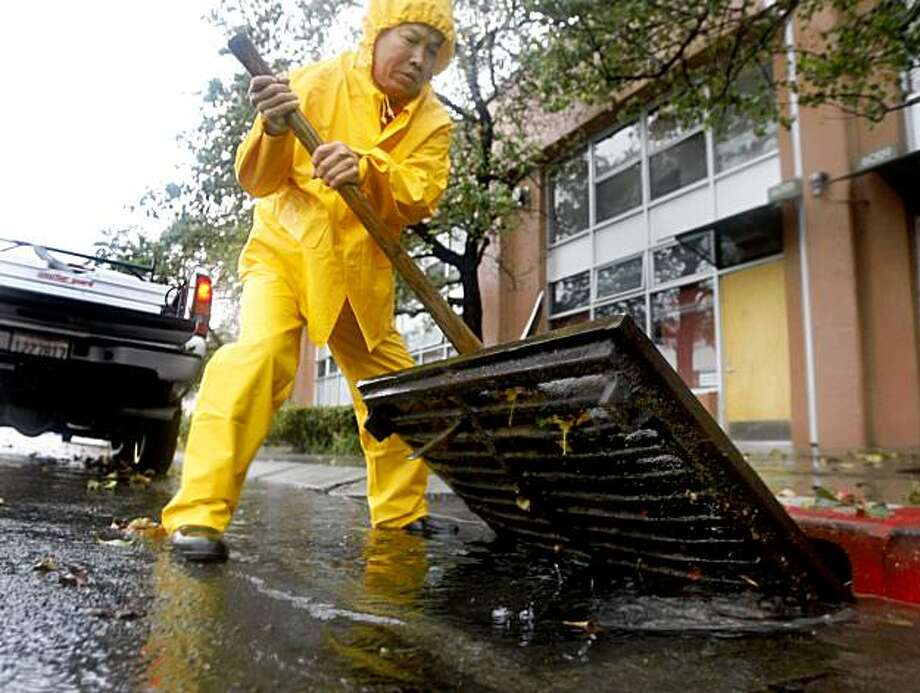 Public works employee Thuch Lang clears a flooded storm drain on Christie Street in Emeryville on Tuesday. Photo: Paul Chinn, The Chronicle