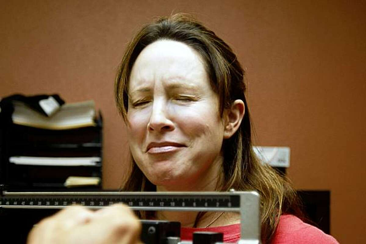 Cecilia Marosi-Hopkins closes her eyes during the first weigh-in before starting a 6 week fitness program at Fitness 101 gym in Menlo Park, Calif., on Thursday, October 1, 2009.