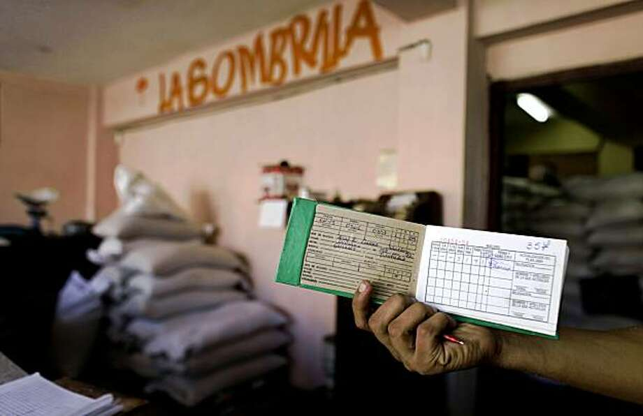 A customer displays his ration card as he waits to buy food a government store in Havana, Friday, Oct. 9, 2009.  Cuba may soon be saying adios to ration cards, the system that allows islanders to buy food at deeply subsidized prices.  The monthly system has long been one of the central building blocks of the country's socialist system, providing everyone from doctors to janitors the same allotment of basic foods like rice, beans, and a bit of chicken. (AP Photo/Javier Galeano) Photo: Javier Galeano, AP