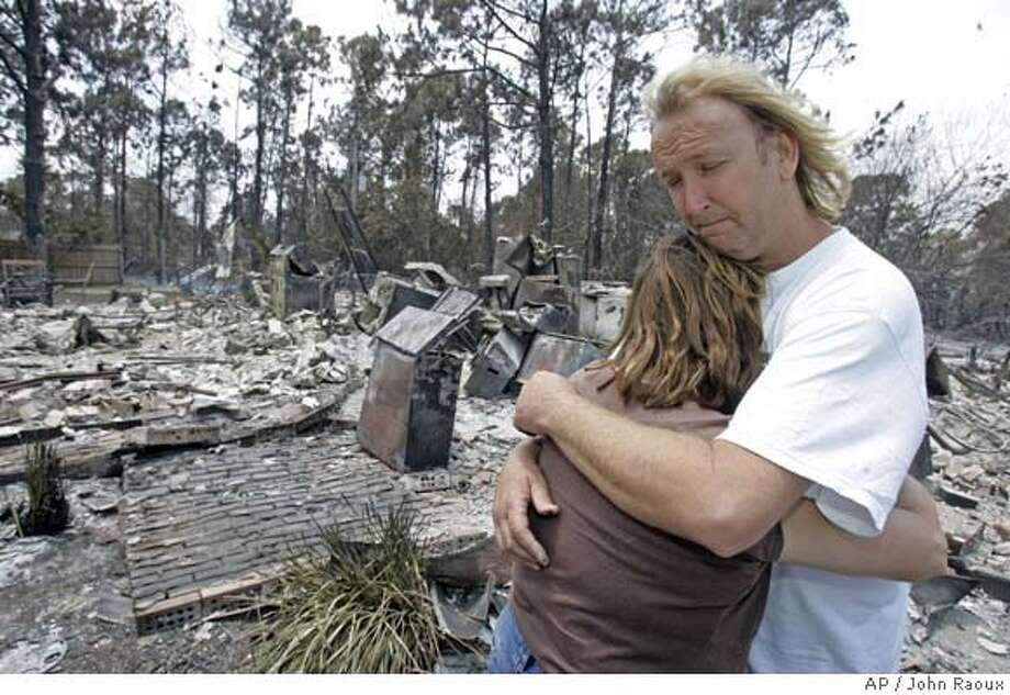 ###Live Caption:Dean Serencko, right, holds fiance, Jacqueline Pedercini, in front of the home they share that was destroyed by wildfires in Palm Bay, Fla., Wednesday, May 14, 2008. (AP Photo/John Raoux)###Caption History:Dean Serencko, right, holds fiance, Jacqueline Pedercini, in front of the home they share that was destroyed by wildfires in Palm Bay, Fla., Wednesday, May 14, 2008. (AP Photo/John Raoux)###Notes:###Special Instructions: Photo: John Raoux