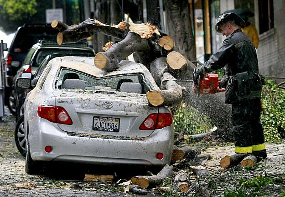 A San Francisco fireman cuts the remaining limbs off a car that was crushed on Hyde Street, that also stopped cable cars that use the nearby tracks on Tuesday, October 13, 2009. Photo: Brant Ward, The Chronicle