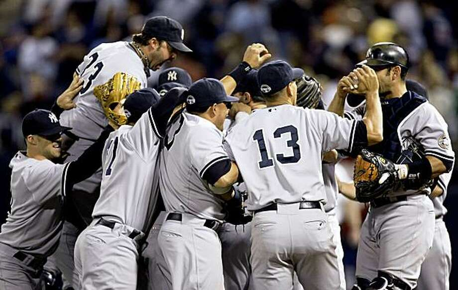 The New York Yankees celebrate after defeated the Minnesota Twins 4-1 in Game 3 of the American League division baseball series Sunday, Oct. 11, 2009, in Minneapolis. The Yankees swept the series. (AP Photo/Charlie Neibergall) Photo: Charlie Neibergall, AP