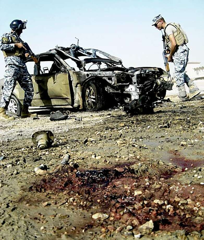 Iraqi security forces inspect a damaged car after a car bomb attack in Ramadi, 115 kilometers (70 miles) west of Baghdad, Iraq, Sunday Oct. 11, 2009.  A series of bombings killed at least 19 people and wounded 60 Sunday in the western Iraqi city of Ramadi, said police and hospital officials, a worrying sign that violence may be on the rise. (AP Photo) Photo: STR, AP
