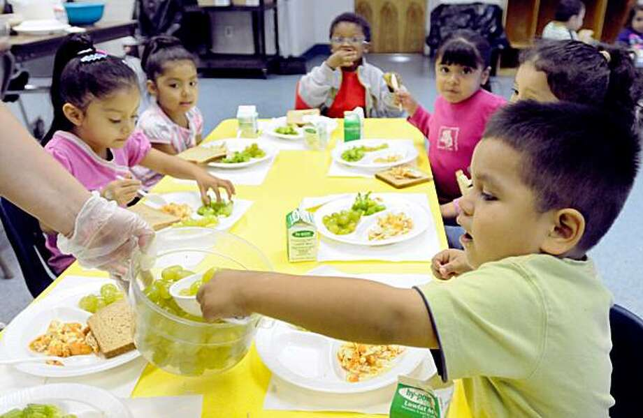 In this photograph taken Friday, Oct. 2, 2009, Jean Carlos Rubell, 3, helps himself to grapes during preschool lunch at the Latin American Community Center in Wilmington, Del. (AP Photo/ Steve Ruark) Photo: Steve Ruark, AP