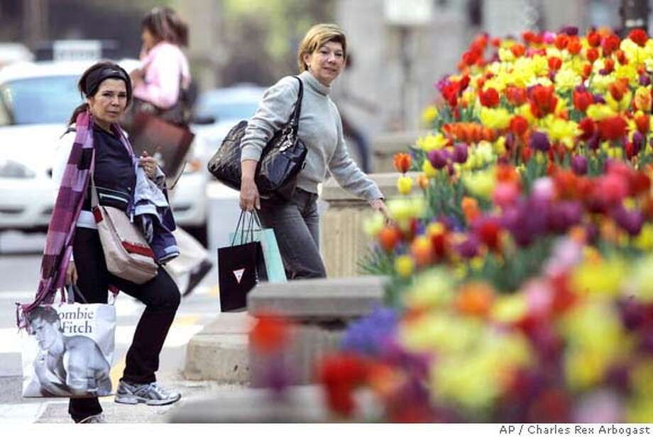 A pair of shoppers look at tulips on Chicago's Michigan Avenue on Tuesday, May 13, 2008. Retail sales dipped in April, but outside of auto sales the retail sector showed strength, rising by a surprisingly strong 0.5 percent. This better-than-expected showing outside of autos was seen as evidence that the consumer is hanging tough even in the face of soaring gasoline prices and a slumping economy. (AP Photo/Charles Rex Arbogast) Photo: Charles Rex Arbogast