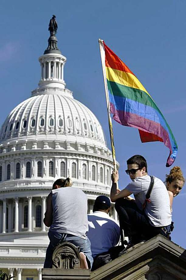 Daniel Raeder, 17, of Rockville, Md., holds a rainbow flag by the Capitol as thousands of gay rights advocates rally in Washington, on Sunday, Oct. 11, 2009. Photo: Jacquelyn Martin, AP