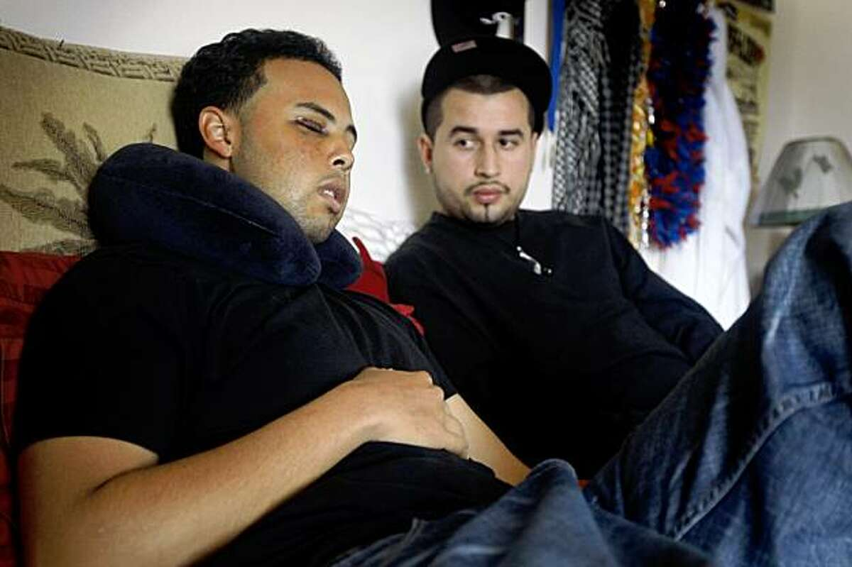 Chris Borgzinner (left) visits with his friend Alex Hernandez while Borgzinner recuperates at home in San Francisco, Calif., on Thursday, Oct. 8, 2009 after several assailants beat him up while riding on the number 9 San Bruno Muni bus last Monday.