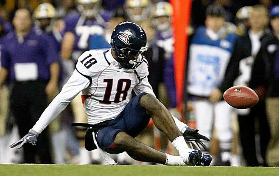 A pass to Arizona's Delashaun Dean bounces off his shoe and subsequently lands in the hands of Washington's Mason Foster for a Husky interception in the 4th quarter on Saturday, Oct. 10, 2009 at Husky Stadium. Foster would take the ball all the way into the endzone for a score to seal the 36-33 come-from-behind victory for the Huskies.  (AP Photo/John Lok - Seattle Times) Photo: John Lok, AP