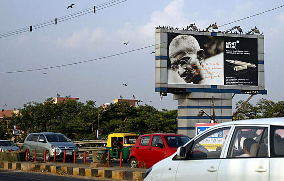 Traffic moves past a billboard displaying a portrait of Mohandas Gandhi, the ascetic father of India's independence, besides an image of a Montblanc pen, in New Delhi, India, Thursday, Oct. 1, 2009. German luxury penmaker Montblanc International GMBH launched a 17,000 euros ($24,763) limited-edition commemorative fountain pen in honor of Gandhi, the man who shunned foreign-made products, leaving some Indians puzzled and others angry. (AP Photo/Mustafa Quraishi) Photo: Mustafa Quraishi, AP
