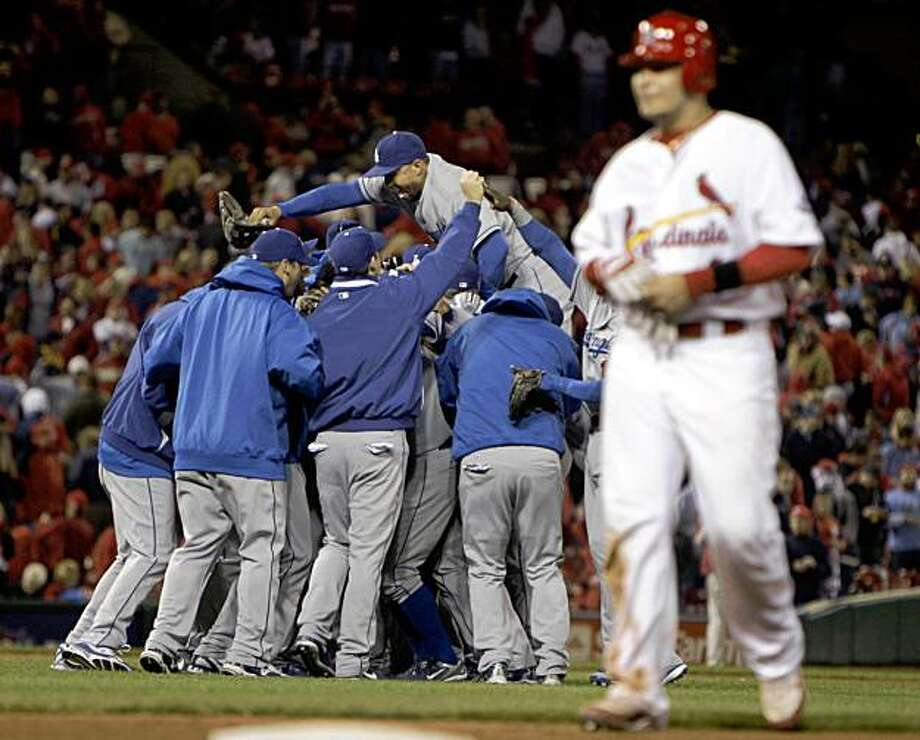 St. Louis Cardinals' Yadier Molina, right, walk off the field as the Los Angeles Dodgers celebrate their victory in Game 3 of the National League division baseball series Saturday, Oct. 10, 2009, in St. Louis. The Dodgers won the game 5-1 to sweep the Cardinals and advance to the National League Championship Series. (AP Photo/Jeff Roberson) Photo: Jeff Roberson, AP