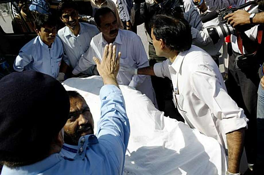 Hospital employees carry the body of a woman killed in a suicide attack in Islamabad, Pakistan, on Monday, Oct. 5, 2009. A bomber disguised as a security officer blew himself up Monday in the lobby of the U.N. food agency in Islamabad, a day after the new leader of the Pakistani Taliban vowed fresh attacks, authorities and witnesses said. (AP Photo/Alexandre Meneghini) Photo: Alexandre Meneghini, AP