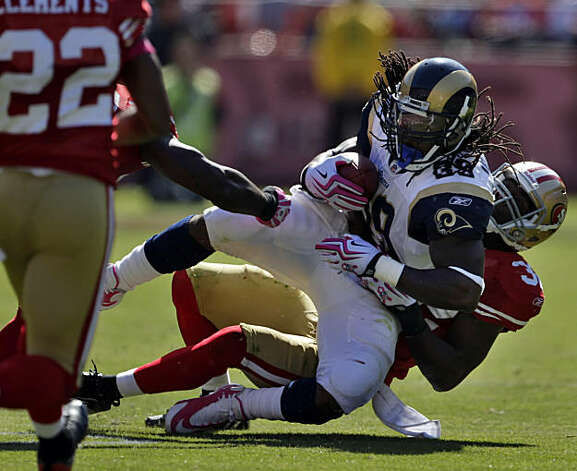 The 49ers' Michael Lewis brings down the Rams' Steven Jackson in the second quarter at Candlestick Park in San Francisco on Sunday. Photo: Carlos Avila Gonzalez, The Chronicle