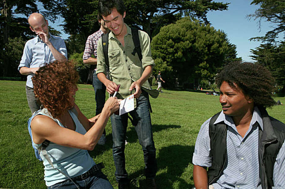 From left, Sam Lavigne and Sean Mahan watch as Ian Kizu-Blair asks stranger Mary Campisi and Miguel Vargas to mail a post card that Kizu-Blair stamped and addressed to his girlfriend in Alamo Square in San Francisco, Calif. on Saturday, September 19, 2009.  .  Interacting with strangers is one of the tasks on the trio's website SFZero.   Kat Wade / Special to the Chronicle Photo: Kat Wade, Special To The Chronicle / SFC