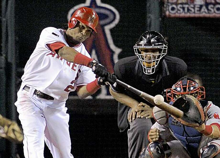 Los Angeles Angels' Erick Aybar hits a two-run RBI triple as Boston Red Sox catcher Victor Martinez catches during the seventh inning of Game 2 of the American League division baseball series, Friday, Oct. 9, 2009, in Anaheim, Calif. (AP Photo/Mark J. Terrill) Photo: Mark J. Terrill, AP