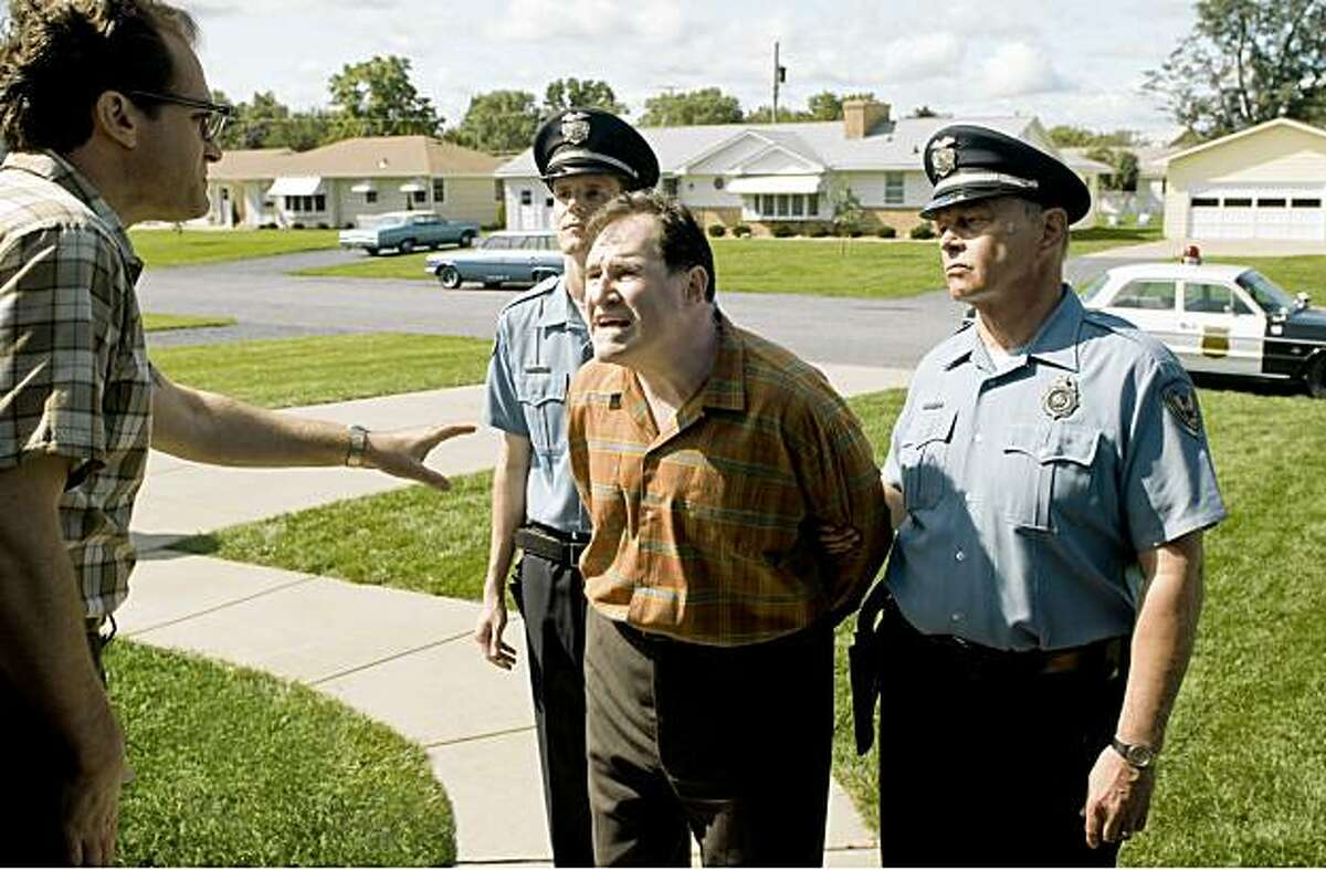 Michael Stuhlbarg (at left, in foreground) stars as Larry Gopnik and Richard Kind (at right, in foreground) stars as Larry's brother Arthur in writer/directors Joel and Ethan Coen's 1967-set A SERIOUS MAN, a Focus Features release.