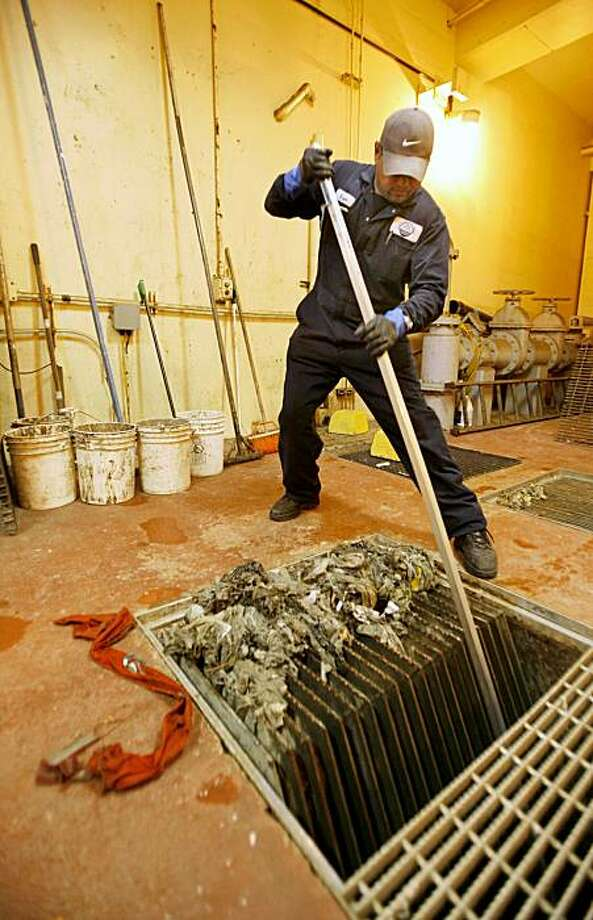 Veer Ram, a plant operator at the South Bayside Systems Authority treatment plant in Redwood City rakes out debris from the screens in the pump station. The scrap of orange is from the county jail on June 27, 2007. Photo: Michael Maloney, The Chronicle