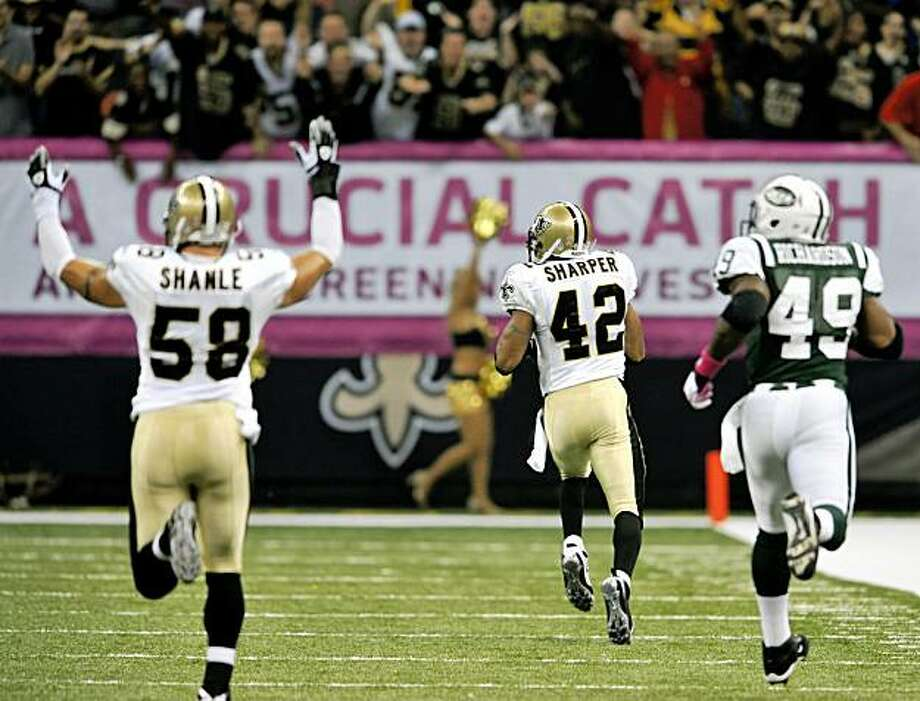 New Orleans Saints linebacker Scott Shanle (58) signals touchdown as safety Darren Sharper heads to the endzone with an interception against the New York Jets in and NFL football game in New Orleans, Sunday, Oct. 4, 2009. New York Jets running back Tony Richardson (49) gives chase. (AP Photo/Bill Feig) Photo: Bill Feig, AP