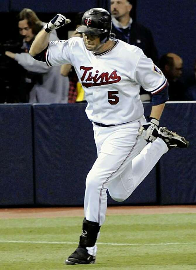 Minnesota Twins' Michael Cuddyer rounds the bases after his tie-breaking solo home run off Kansas City Royals Dusty Hughes in the eighth inning of a baseball game Saturday, Oct. 3, 2009, in Minneapolis. The Twins won 5-4. (AP Photo/Jim Mone) Photo: Jim Mone, AP