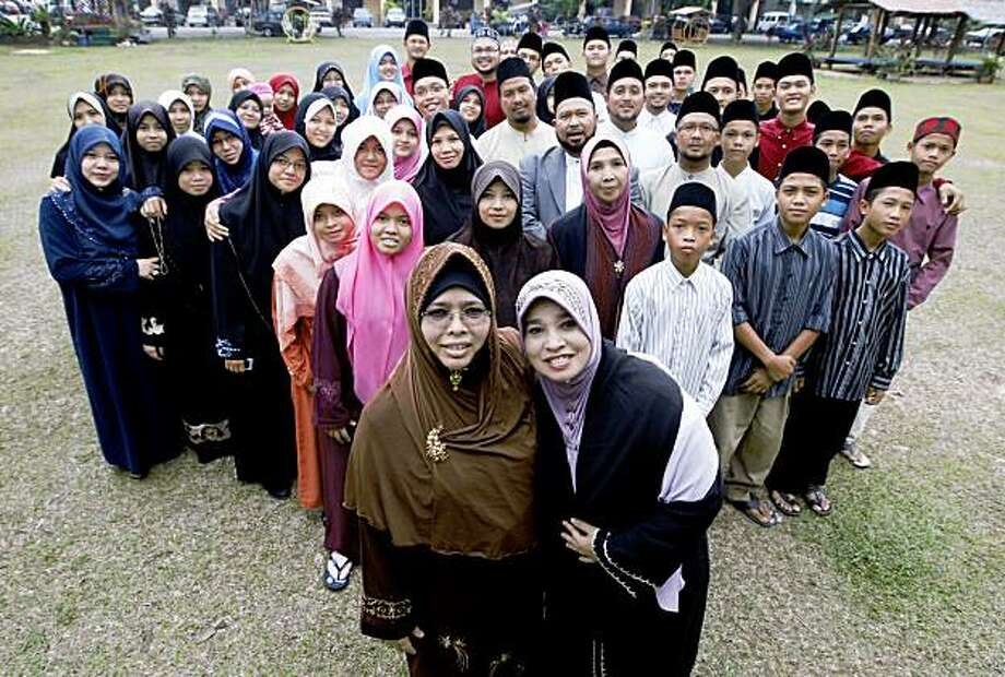 In this  Aug. 12, 2009 photo, Hatijah Aam, front left, and Nor Aziah Ibrahim, both wives of Ashaari Muhammad, are pictured with some of their extended family in Rawang, north of Kuala Lumpur, Malaysia. Polygamy is legal for Muslims in Malaysia, though not widespread. The Ashaari clan believes it should be. Last month, the sprawling family launched a Polygamy Club that seeks to promote plural marriages for what it says are noble aims, such as helping single mothers, prostitutes and older women find husbands. (AP Photo/Mark Baker) Photo: Mark Baker, AP