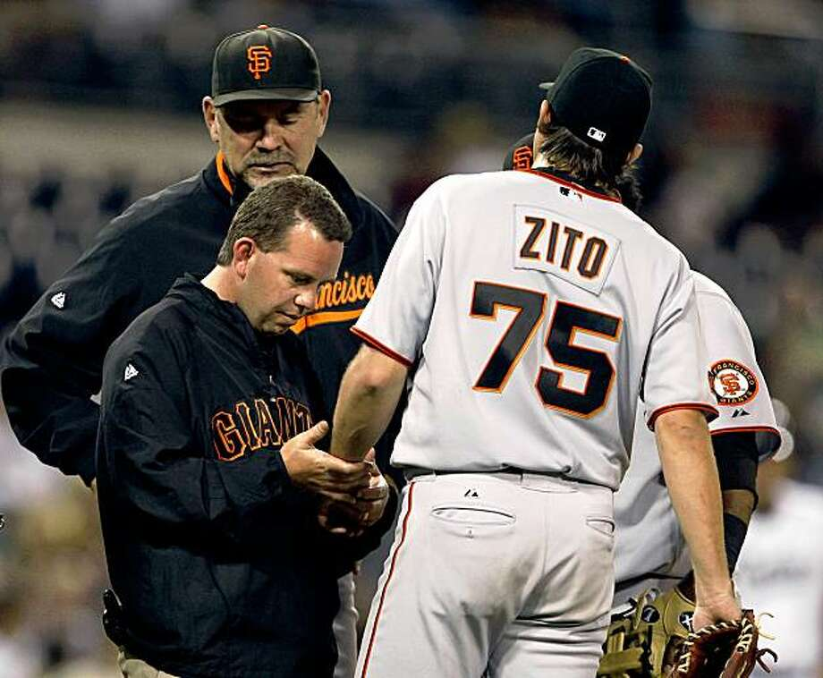 San Francisco Giants' Barry Zito is examined by a member of the Giants' training staff as manager Bruce Bochy looks on after Zito was struck in his left arm by a line drive hit by San Diego Padres' Adrian Gonzalez in the sixth inning of a baseball game  Friday, Oct. 2, 2009 in San Diego. Photo: Lenny Ignelzi, AP