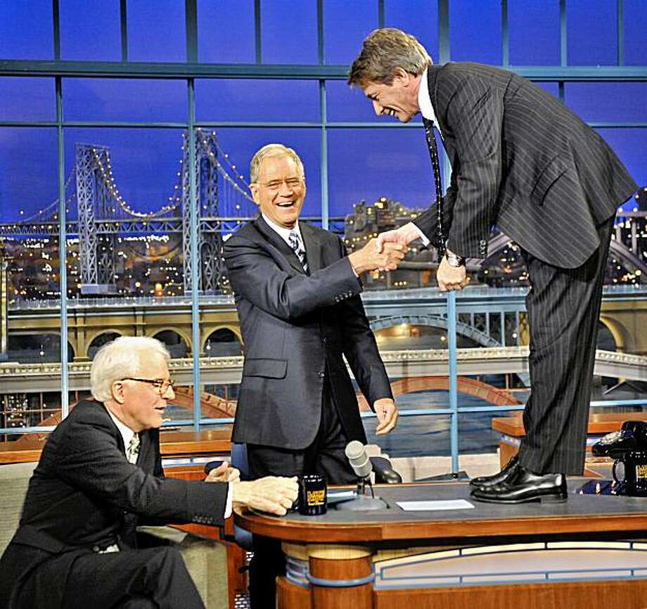 """In this publicity image released by CBS, Steve Martin, left, is seated as Martin Short shakes hands with host David Letterman, center, during a taping of """"The Late Show with David Letterman,"""" on Monday, Oct. 5, 2009, in New York. (AP Photo/CBS, John Paul Filo) Photo: John Paul Filo, AP"""