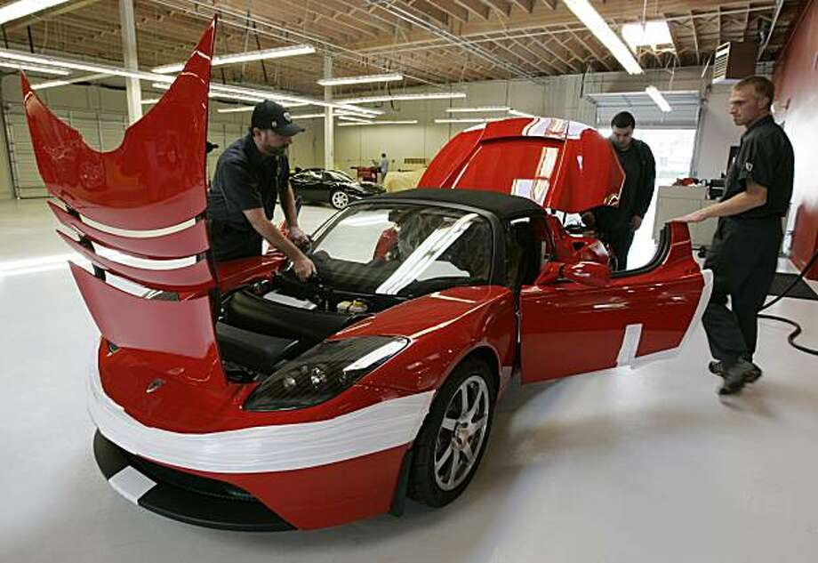 FILE - In this Sept. 16, 2008 file photo, workers assembly a Tesla Roadster at their showroom in Menlo Park, Calif. Tesla Motors will open a new power train production facility and corporate headquarters in Palo Alto, Calif., as the electric-car maker moves to expand production after a recent award of government loans, the company said Tuesday, Aug. 18, 2009. (AP Photo/Paul Sakuma, file) Photo: Paul Sakuma, AP