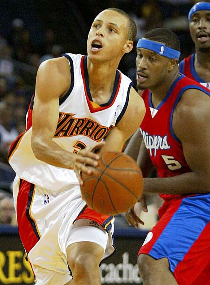 Golden State Warriors' Stephen Cuury drives to the basket past Los Angeles Clippers' Craig Smith during the first half of an NBA preseason basketball game, Sunday, Oct. 4, 2009 in Oakland, Calif. (AP Photo/George Nikitin) Photo: George Nikitin, AP