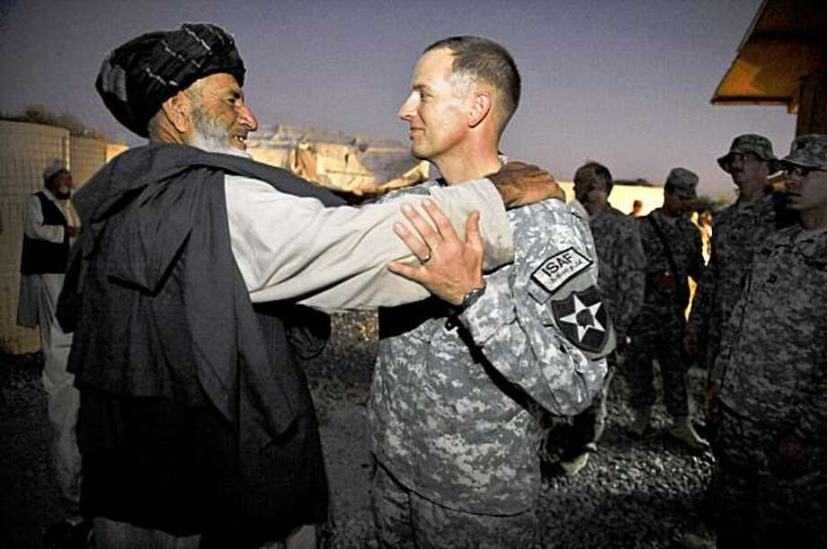 US military commander Lieutenant Colonel William Clark and an unidentified Afghan tribal leader (L) embrace each other at the conclusion of a conference of tribal leaders of Spin Boldak at Camp Costell at the forward operating base of the NATO-led International Security Assistance Force in Spin Boldak, southern Afghanistan. Colonel Clark commander of the US Army's 5th Stryker Brigade Combat Team, 2nd Infantry Division , 8-1 Cavalry Squadron held a dialogue with 34 tribal leaders to provide economic and security assistance to local communities as part of the counter insurgency strategy to defeat the Taliban.  AFP PHOTO / ROMEO GACAD (Photo credit should read ROMEO GACAD/AFP/Getty Images) Photo: ROMEO GACAD, AFP/Getty Images