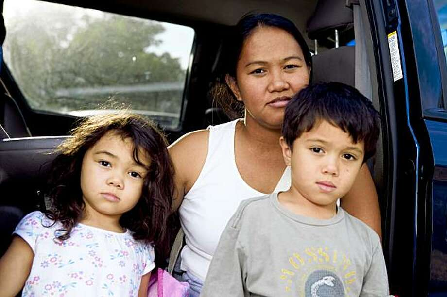 Home buyer Judith Goul poses for a photo with four year-old daughter Jillienne Angel, left, and son Jeremiah, 5, right, on the driveway of her rental home in Fairfield, Calif. on Monday, Sept. 28, 2009. Goul, whose husband is currently serving overseas in the military, recently bid $170,000 on a bank-owned home in Fairfield but lost out to an investor who paid only $120,000 but in all cash. Many bank-owned homes say up front that VA and FHA offers are not welcome. Photo: Stephen Lam, The Chronicle