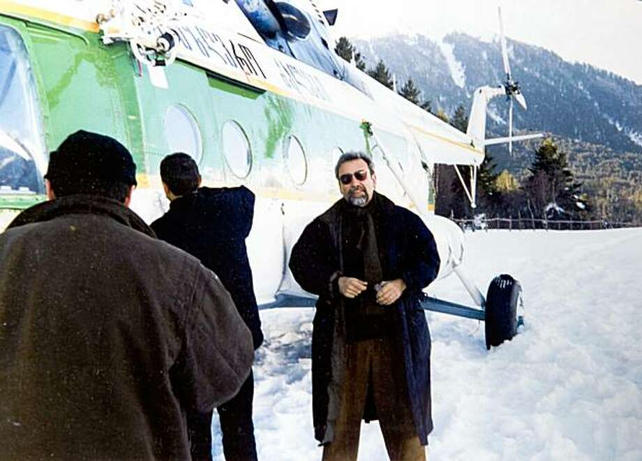 **ADVANCE FOR WEEKEND RELEASE, OCT. 3-4** This undated photo released by Paul Joyal shows Paul Joyal, right, standing next to a Georgian helicopter with members of the Georgian Border Guard near the Georgian border with Chehnya. Joyal, an expert on Russia and frequent critic of its leaders, was shot outside of his home on March 1, 2007. Police assumed that Joyal was the victim of a random street crime. But Joyal soon confronted another possibility, for years, he had warned that the Russian government was taking extreme steps, including assassinations, to silence its critics. Perhaps he too had become a target. (AP Photo/Paul Joyal) **NO SALES** Photo: AP