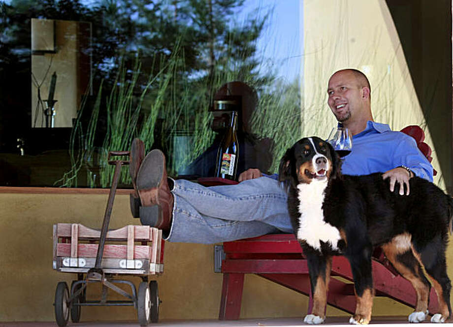 MacPhail puts his feet up on his first red wagon (a logo for his winery) and enjoys the attention of his dog Zuni at his home at the winery. Winemaker James MacPhail at his Healdsburg winery on Magnolia Drive just off Westside Thursday September 24, 2009. Photo: Brant Ward, The Chronicle