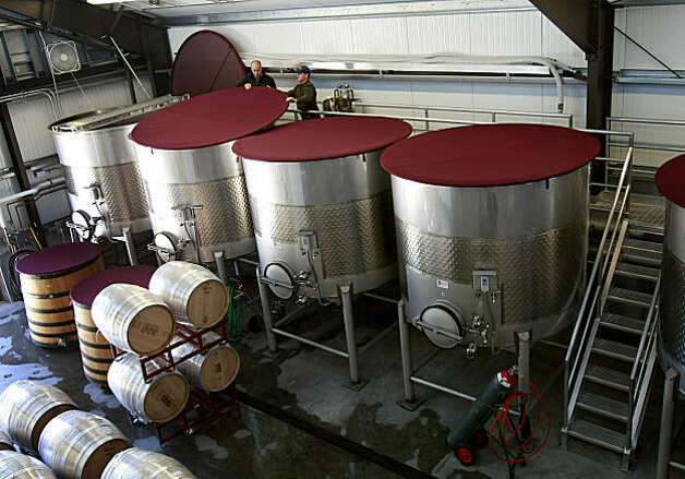 MacPhail and a colleague check on the fruit in the huge steel vats at his winery. Winemaker James MacPhail at his Healdsburg winery on Magnolia Drive just off Westside Thursday September 24, 2009. Photo: Brant Ward, The Chronicle