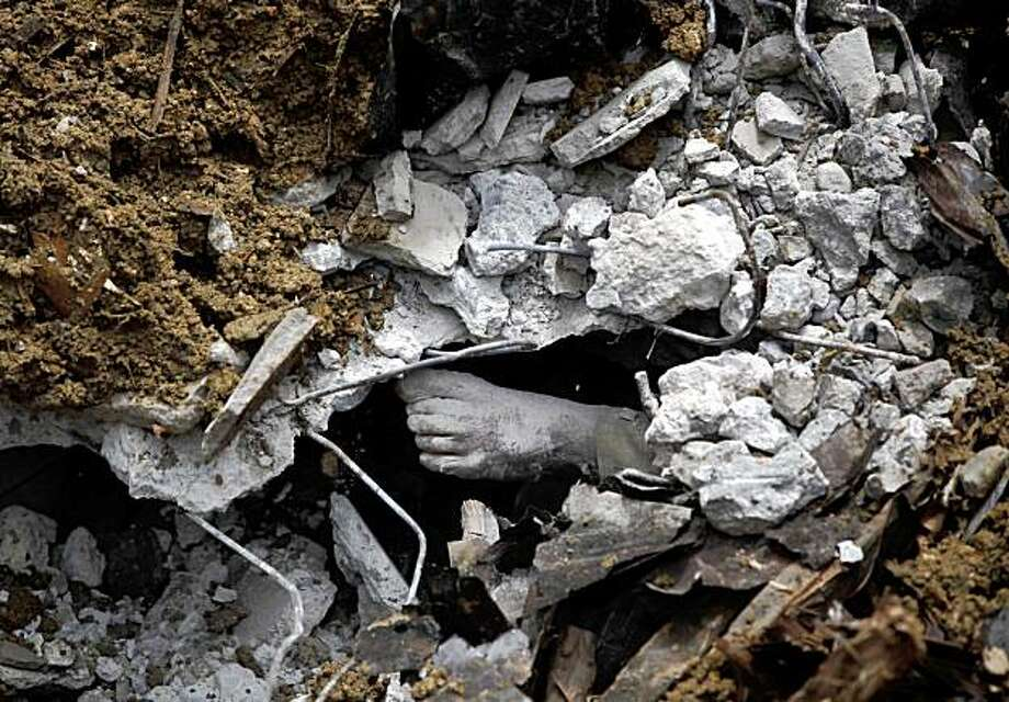 The foot of an Indonesian villager who was buried in a landslide following last Wednesday's earthquake is seen as rescuers try to remove the body in the Sumatran Island  village of Jumanak, in Padang Pariaman, Sunday, Oct. 4, 2009. Officials said hundreds of people were buried and presumed dead in the hillside villages in Padang Pariaman district on the western coast of Sumatra island following the 7.6 magnitude earthquake last week. (AP Photo/Kevin Frayer) Photo: Kevin Frayer, AP