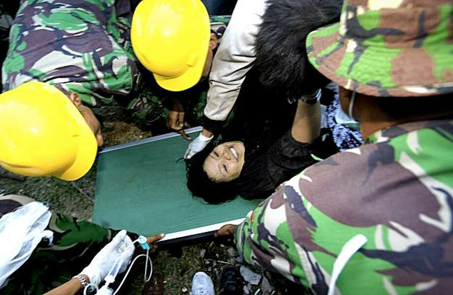 ** CORRECTS NAME OF SURVIVOR ** Indonesian rescue team pulled out a survivor, Suci Ravika Wulan Sari, who was trapped in a building since Wednesday's earthquake in Padang, Indonesia on Friday, Oct. 2, 2009. Two days after the quake that toppled thousands of buildings on Sumatra island, stricken residents in a district north of the hard-hit city of Padang, had yet to receive help. (AP Photo/Wong Maye-E) Photo: Wong Maye-E, AP