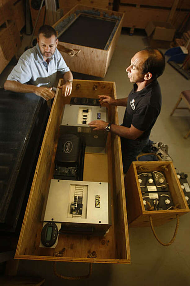 Keith Begg (l to r), Project leader Niassa Lion Project Mozambique and Stephen Gold discuss the contents of a solar power kit in San Francisco, Calif. on Tuesday, September 29, 2009 where it was assembled by Gold to be sent over to Africa. Photo: Lea Suzuki, The Chronicle