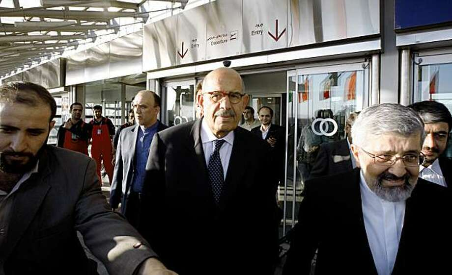 Head of the International Atomic Energy Agency, Mohamed ElBaradei, center, makes his way, as he is accompanied by Iran's envoy to the IAEA, Ali Asghar Soltanieh, right, while he leaves the Imam Khomeini airport south of the capital Tehran, Iran, Saturday, Oct. 3, 2009. ElBaradei arrived in Iran to arrange an inspection of the uranium enrichment facility near the holy city of Qom. (AP Photo/Vahid Salemi) Photo: Vahid Salemi, AP