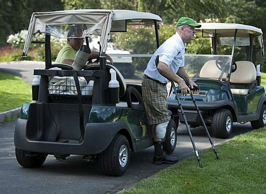 Ken Green, right, prepares to walk from a golf cart at a charity golf tournament on Monday, Sept. 28, 2009, at the Ridgewood Coutry Club in Danbury, Conn. The Friends of Ken Green Benefit Tournament is raising money for the Ken Green Living Expenses Trust. (AP Photo/Douglas Healey) Photo: Douglas Healey, AP