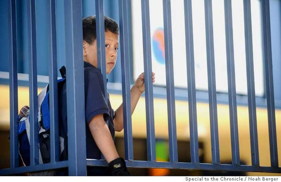 Javier Alfredo, 7, a second-grader at Stonehurst Elementary School, watches from behind the school�s fence as Oakland politicians and media gather following fears of an immigration raid on Tuesday, May 6, 2008, in Oakland, Calif. EDITOR: I CHECKED WITH THE GUARDIAN PICKING HIM UP. SHE SAYS IT�S OK TO USE NAME, BUT YOU MAY WANT TO LEAVE IT OUT. CALL PHOTOG IF QUESTIONS: (510) 701-3132.  Photo by Noah Berger / Special to the Chronicle Ran on: 05-07-2008  A Stonehurst student, Javier, 7, watches politicians and media gather at his elementary school .  Ran on: 05-07-2008  A Stonehurst Elementary student, Javier, 7, watches politicians and the media gather at his elementary school in Oakland.  Ran on: 05-07-2008  A Stonehurst Elementary student, Javier, 7, watches as politicians and the media gather at his school in Oakland.  Ran on: 05-07-2008  A Stonehurst student, Javier, 7, watches politicians and media gather at his elementary school .  Ran on: 05-07-2008 Photo: Noah Berger