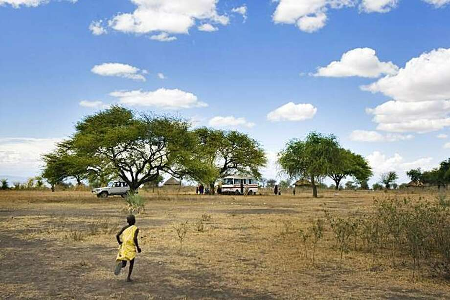 A young Maasai boy runs from his Boma, or village, to where Dr. Frank and his volunteer medical team have set up their mobile clinic to treat the villagers on Thursday, October 31, 2007, outside Mdori, Tanzania. Dr. Frank Artress, a former cardiac anestheA young Maasai boy runs from his Boma, or village, to where Dr. Frank and his volunteer medical team have set up their mobile clinic to treat the villagers on Thursday, October 31, 2007, outside Mdori, Tanzania. Dr. Frank Artress, a former cardiac anesthesiologist from Modesto, Calif., survived a nearly fatal climb on Mount Kilimanjaro nearly five years ago. Since then, he and his wife Susan have returned to Tanzania to heal the people of the country they grew to love and call home. Their work is done for free, through a charitable organization Frank and Susan founded. Photo by Carlos Avila Gonzalez / San Francisco Chronicle Ran on: 05-04-2008 {lcub} Bush doctor {rcub}  A Maasai boy runs from his village to where Dr. Frank Artress and his volunteer medical team have set up a clinic on wheels. After a brush with death on Mount Kilimanjaro, Artress and his wife, Susan Gustafson, moved from Modesto to Tanzania to give back to the people who saved him. Ran on: 05-04-2008 {lcub} Bush doctor {rcub}  A Maasai boy runs from his village to where Dr. Frank Artress and his volunteer medical team have set up a clinic on wheels. After a brush with death on Mount Kilimanjaro, Artress and his wife, Susan Gustafson, moved from Modesto to Tanzania to give back to the people who saved him.   MANDATORY CREDIT FOR PHOTOG AND SAN FRANCISCO CHRONICLE/NO SALES-MAGS OUT Photo: Carlos Avila Gonzalez, The Chronicle