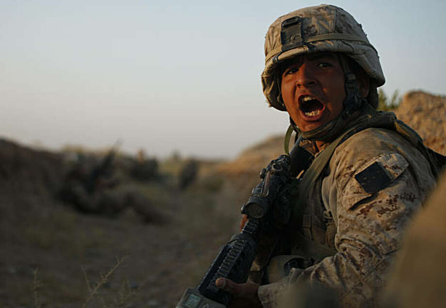 U.S. Marine Lance Cpl. Vincent Morales, of Baytown, Texas, with 3rd Platoon, Bravo Company, 1st Battalion 5th Marines, yells to a fellow Marine inside a dry irrigation canal, in Nawa district, Helmand province, southern Afghanistan, Friday, Oct. 2, 2009. (AP Photo/Brennan Linsley) Photo: Brennan Linsley, AP