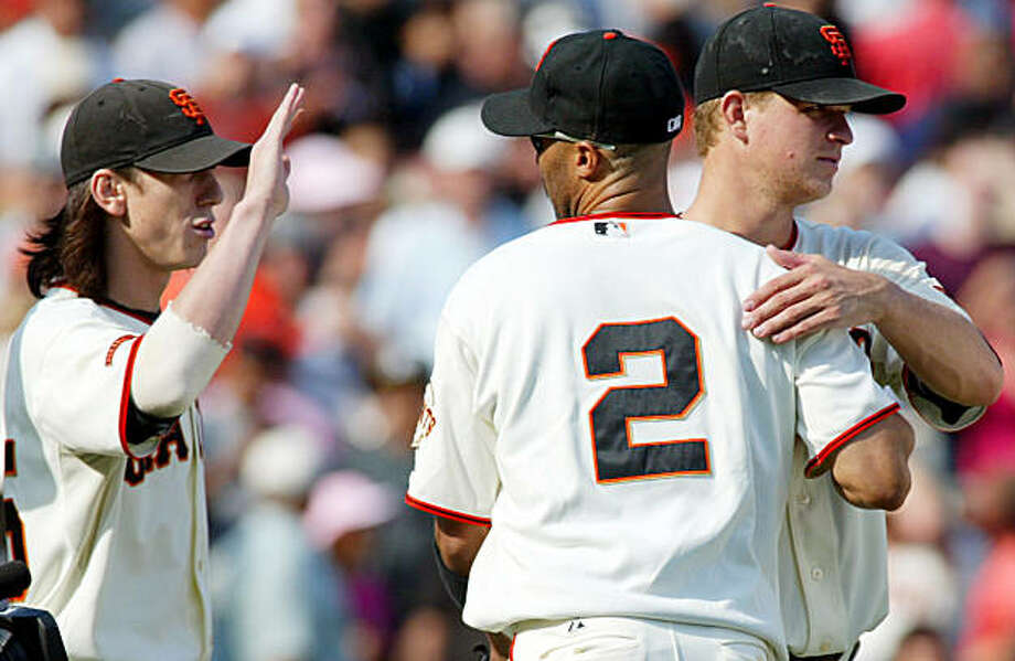 San Francisco Giants pitcher Matt Cain, right, and Randy Winn (2) celebrate as Giants' Tim Lincecum waits for a high five after a baseball game against the Chicago Cubs, Sunday, Sept. 27, 2009 in San Francisco. The Giants beat the Cubs 5-1. (AP Photo/George Nikitin) Photo: George Nikitin, AP