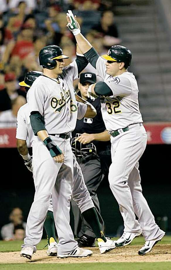 Oakland Athletics designated hitter Jack Cust (32) is congratulated by  Ryan Sweeney, left, after he hit a three-run home run during the fifth inning of a baseball game in Anaheim, Calif., Saturday, Sept. 26, 2009.  (AP Photo/Lori Shepler) Photo: Lori Shepler, AP