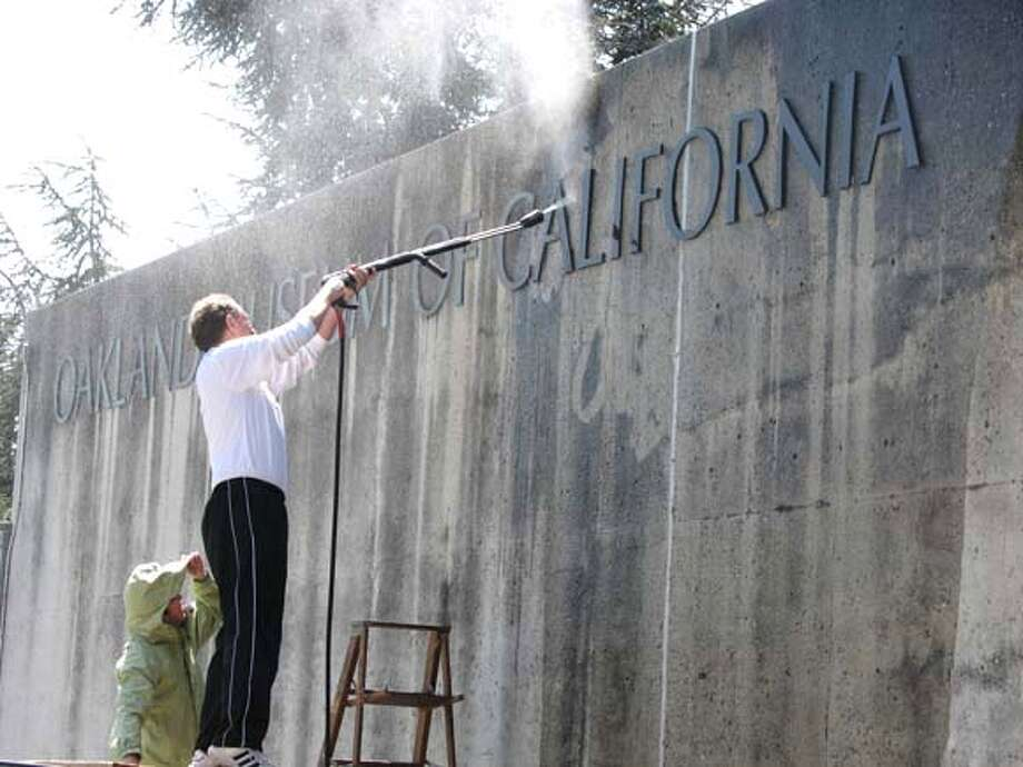 ###Live Caption:Top officials with the Oakland Museum used a water blaster to get rid of grime from their sign that fronts 12th street.###Caption History:Top officials with the Oakland Museum used a water blaster to get rid of grime from their sign that fronts 12th street.###Notes:###Special Instructions: Photo: Jonathan Curiel