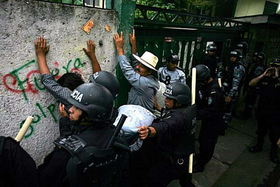 Farmers who support Honduras' ousted President Manuel Zelaya are detained by riot police as they evict them from the National Agrarian Institute where they were squatting in protest of Zelaya's ouster in Tegucigalpa, Wednesday, Sept 30, 2009.  Business and political leaders who backed the coup overthrowing Zelaya now are considering returning him to office with limited powers.  (AP Photo/Rodrigo Abd) Photo: Rodrigo Abd, Associated Press